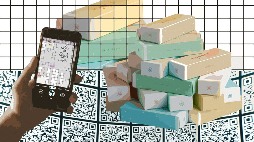 A pile of bars of soaps and someone holding a phone up in front of them.