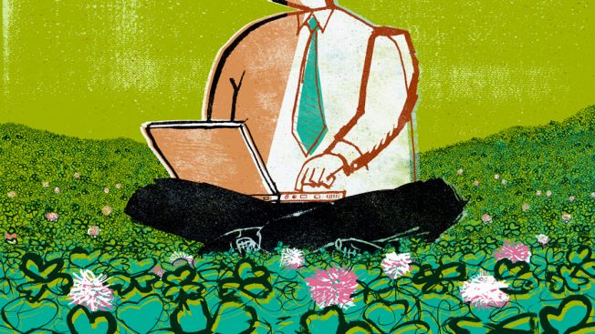 Businessman with laptop sitting on a field of grass and flowers