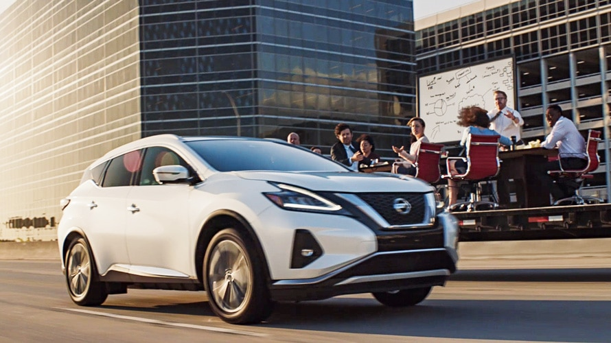white 2020 Murano driving past a group of employees having a meeting outside