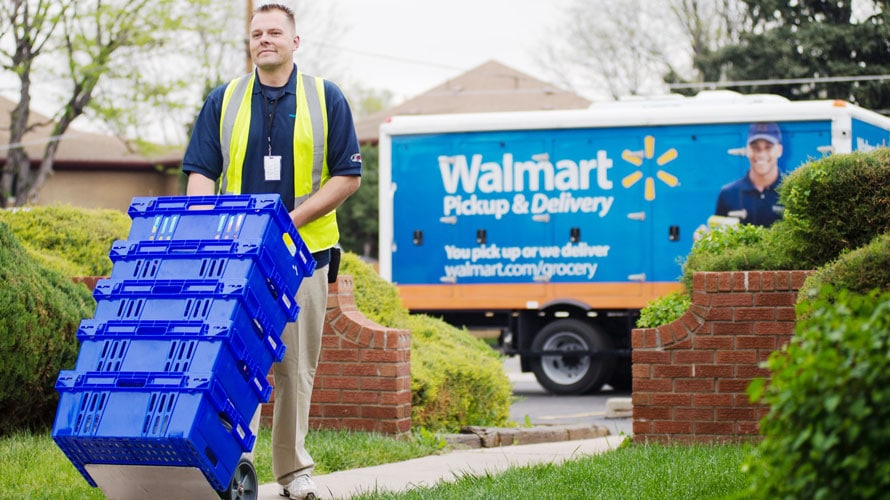 A Walmart employee delivers groceries.