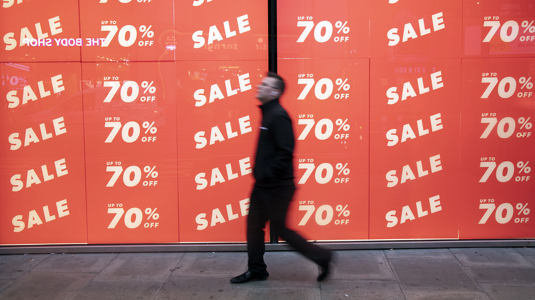People out shopping on Oxford Street walk past large scale January sale signs in red and white for major high street clothing retail shops on 7th January 2019 in London, United Kingdom. Its time for the Winter sales, and most shops are advertising big reductions in prices. Bargains are available and the shopping streets are busy. Oxford Street is a major road in the West End of London. It is Europe's busiest shopping street, with around half a million daily visitors, and has approximately 300 shops.