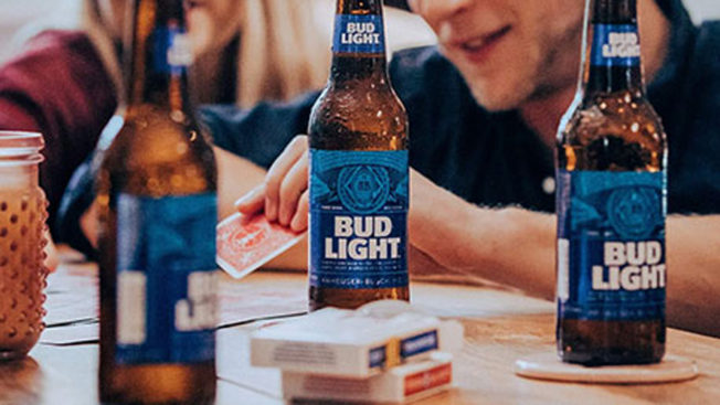 Three bottles of Bud Light with a man holding a playing card behind them