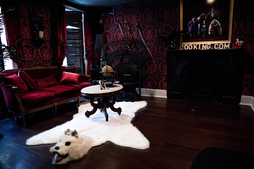 A room in the recreated Addams Family house with dark Victorian wallpaper and a polar bear rug