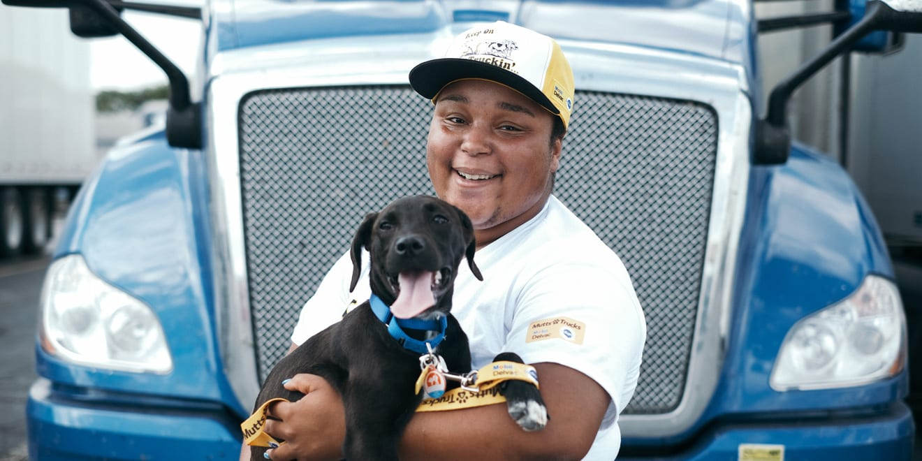 A truck driver holds a dog in front of a truck.