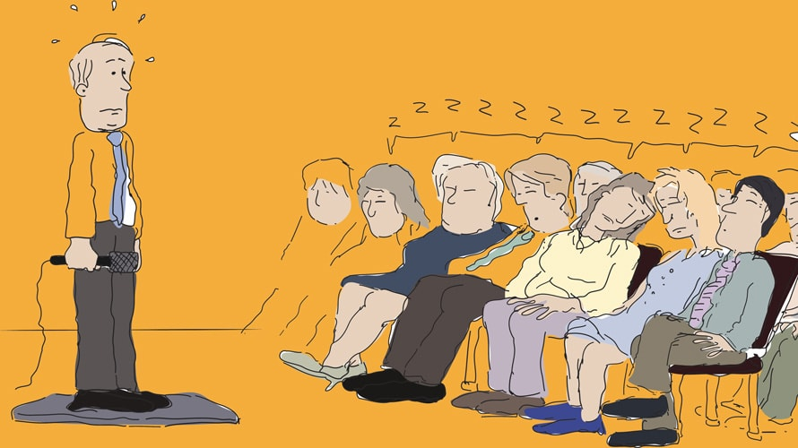 Person holding a microphone in front of a group of people falling asleep