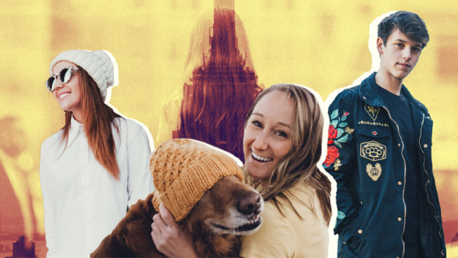 A photo of three people with a woman holding a dog with a yellow hat on in the front