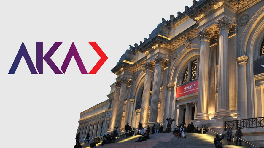 The exterior of the Metropolitan Museum of Art with the AKA NYC logo on the left