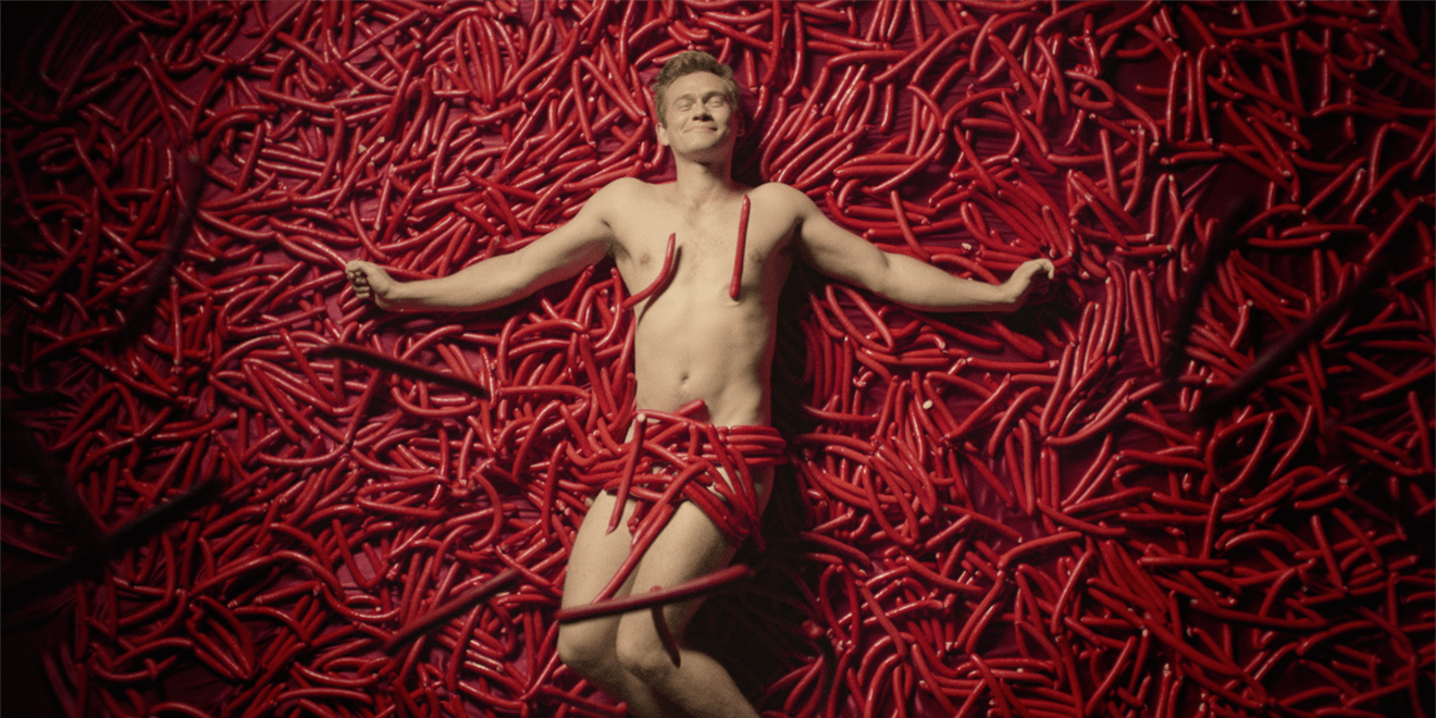 Image from a Danish anti-binge drinking PSA of man lying in a pile of sausages