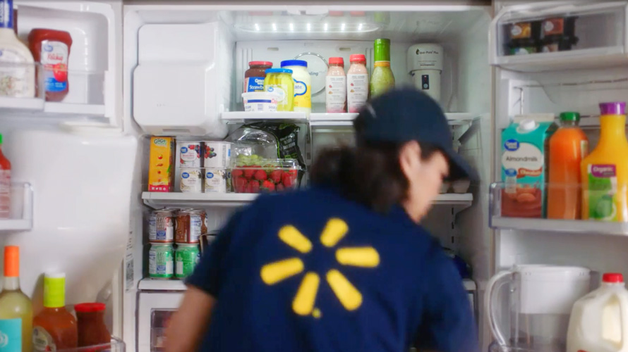 A person in a Walmart vest puts items in a refrigerator.