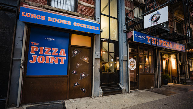 the storefront of the new york knicks-themed restaurant The Pizza Joint