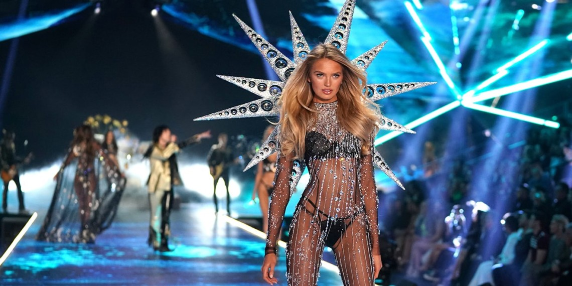 model with long blonde hair (Romee Strijd) walks the runway at the Victoria's Secret 2018 fashion show wearing strings of crystals and spiked