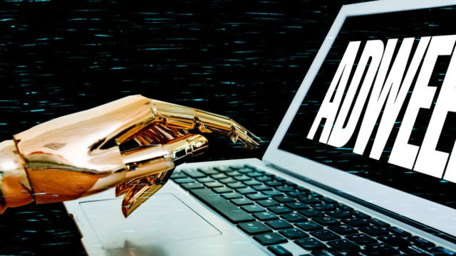 A robot hand hovering over a laptop keyboard with an Adweek logo on the screen
