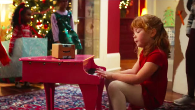 Girl in a red dress sitting at a small pink piano
