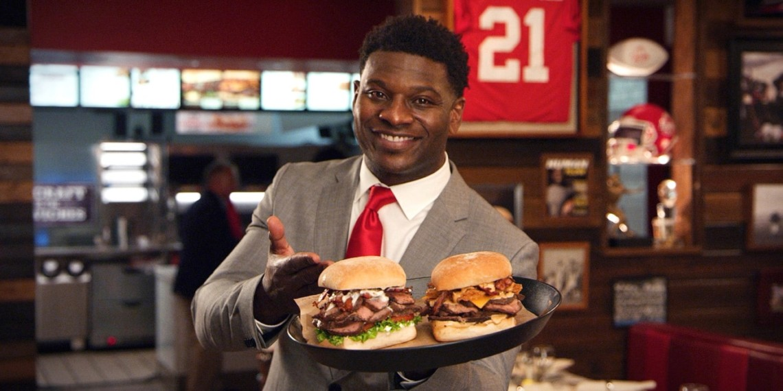 LaDainian Tomlinson in an Arby's showcasing sandwiches