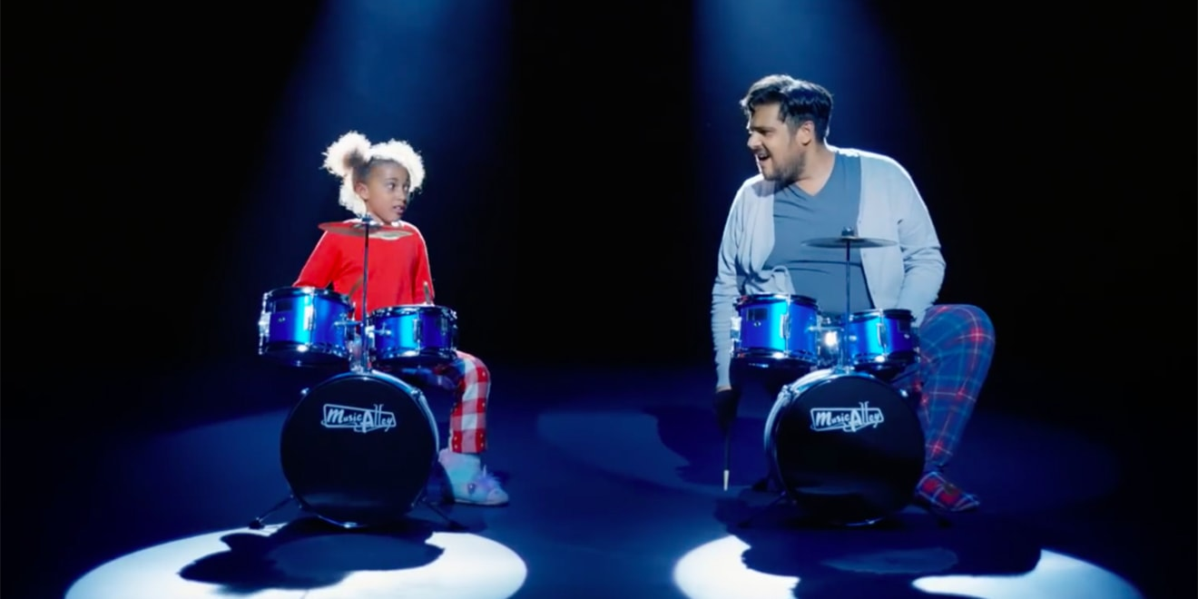 a dad and daughter sitting behind drum sets