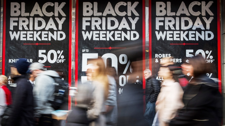 People walking with Black Friday promotional posters in the background