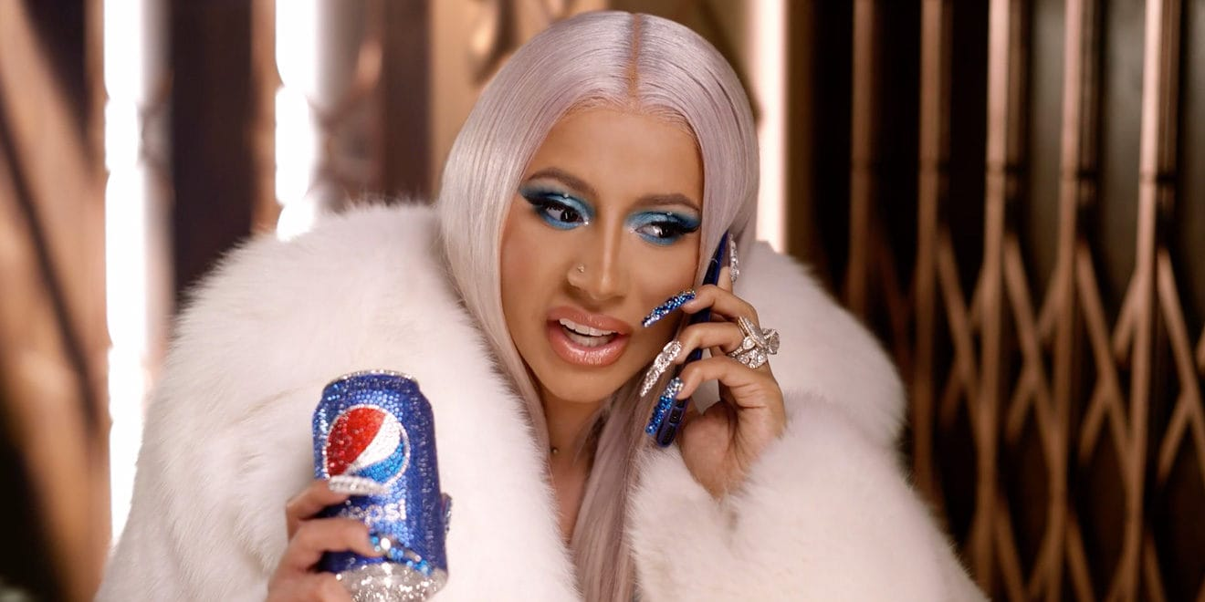 Cardi B on the phone holding a pepsi on the other hand