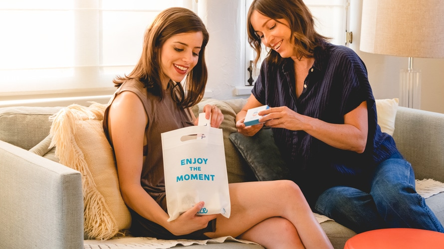 "Two women, one holding an Eaze product and other other holding a bag that says, ""Enjoy the moment."""