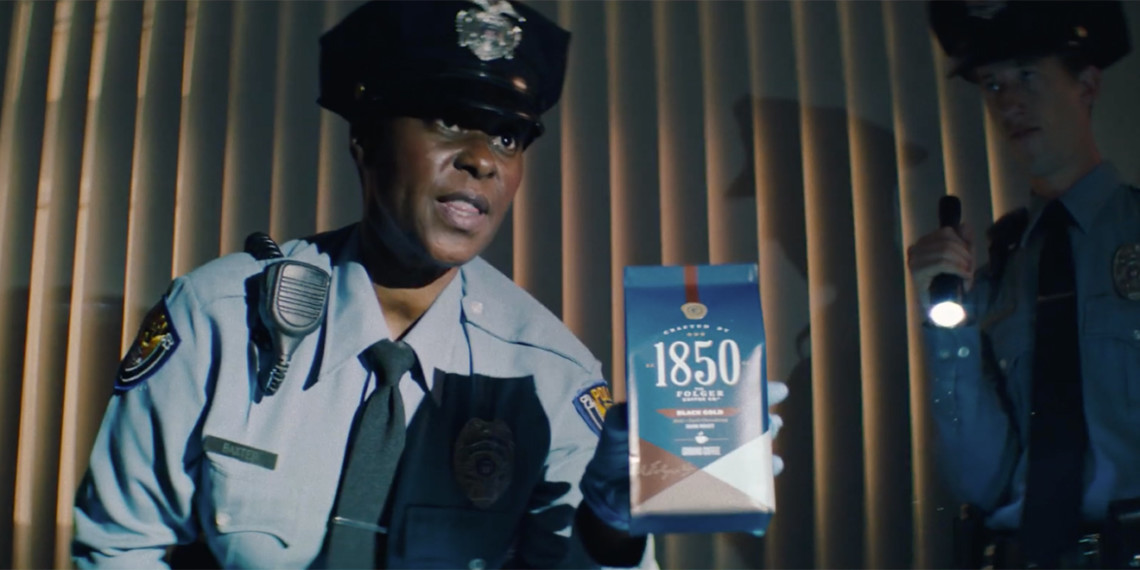 A police officer holding up Folgers 1850 coffee.