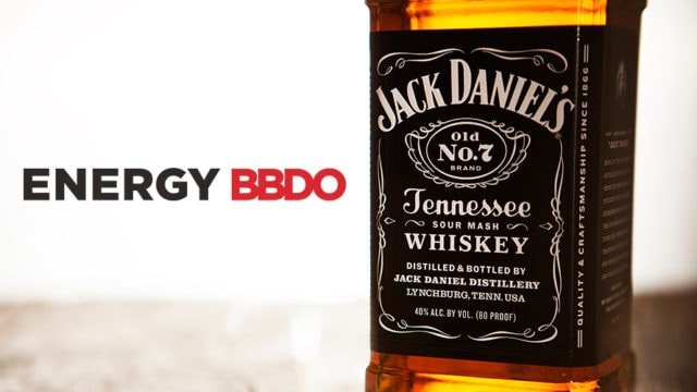the energy bbdo logo next to a bottle of jack daniel's whiskey