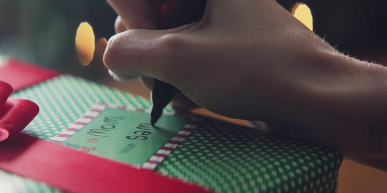 """A closeup of a hand writing """"Sam"""" on a gift that says, """"To Mom."""""""