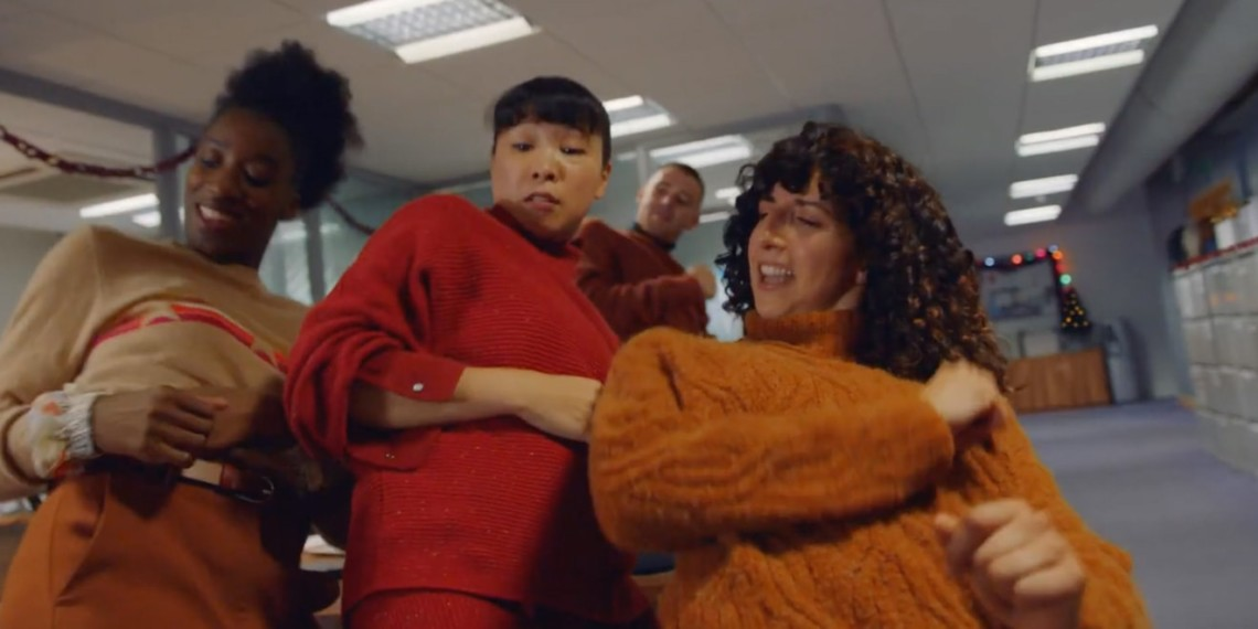 Still from M&S Go Jumpers for Christmas in office campaign