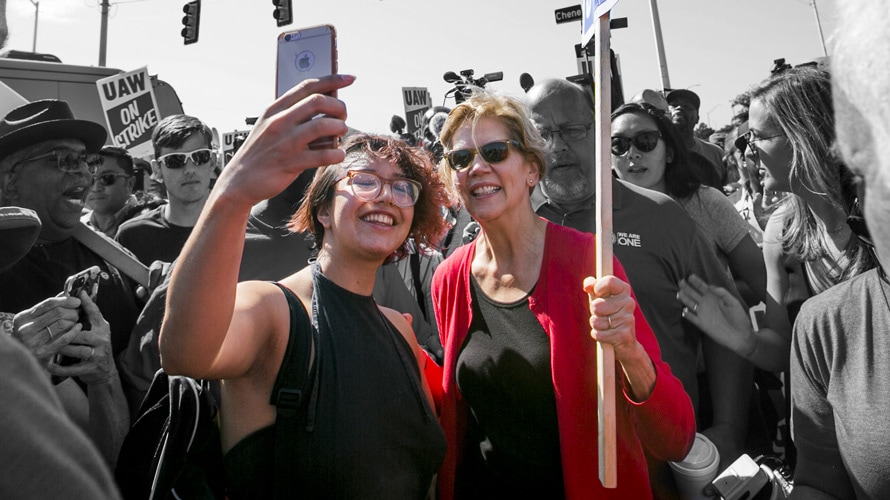 Elizabeth warren at a rally taking a selfie with a fan