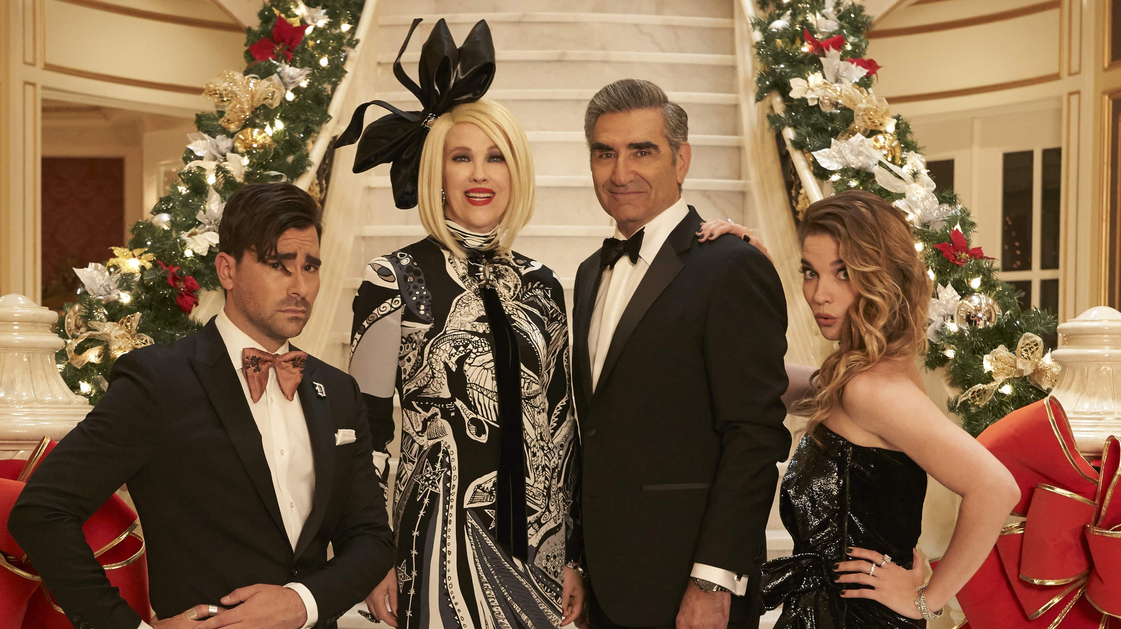 The cast of Schitt's Creek in front of a large staircase decorated for the holidays