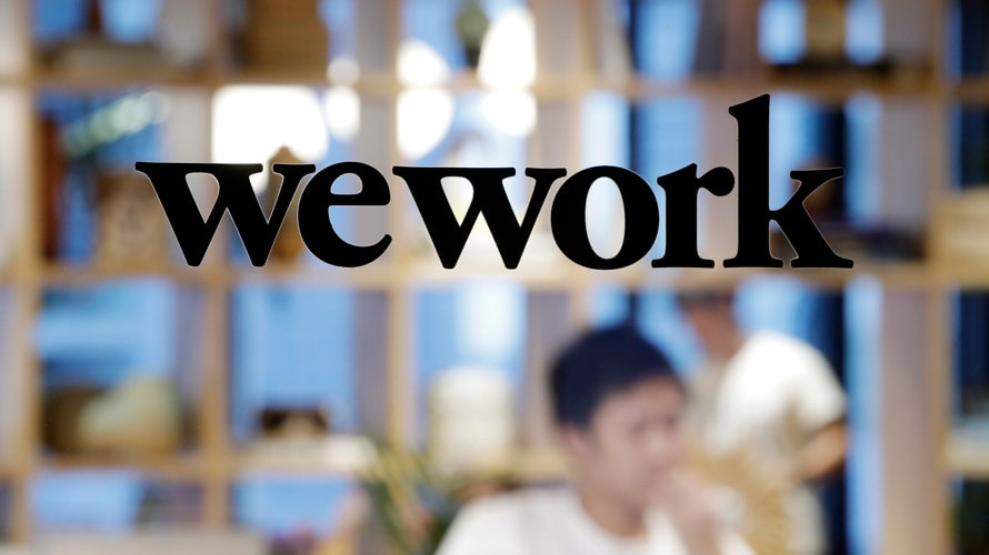 the wework logo on a window looking into a wework office