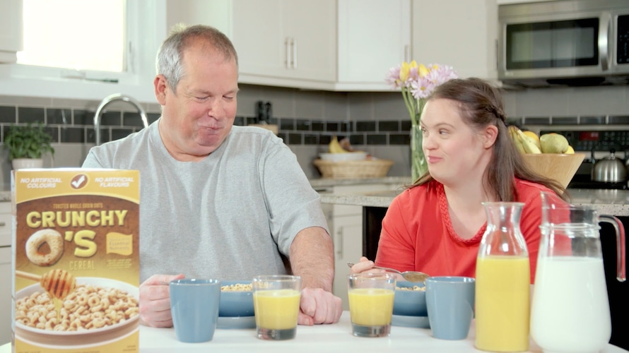 a father and daughter with disabilities eating cereal