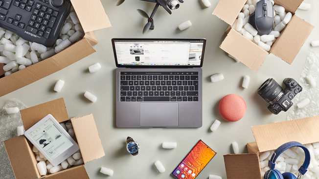 a laptop on a crowded desk full of products