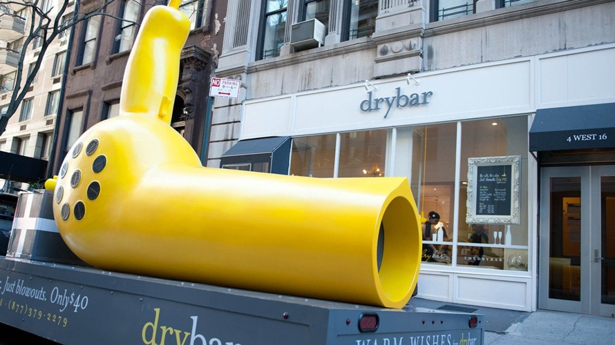 Giant yellow blow dryer in front of a drybar store