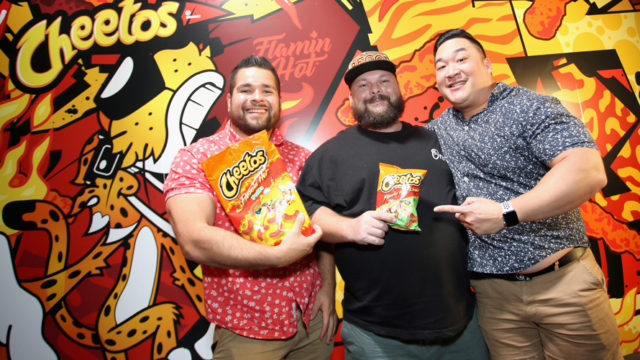 three men standing in front of a cheeto's graffiti holding bags of cheetos