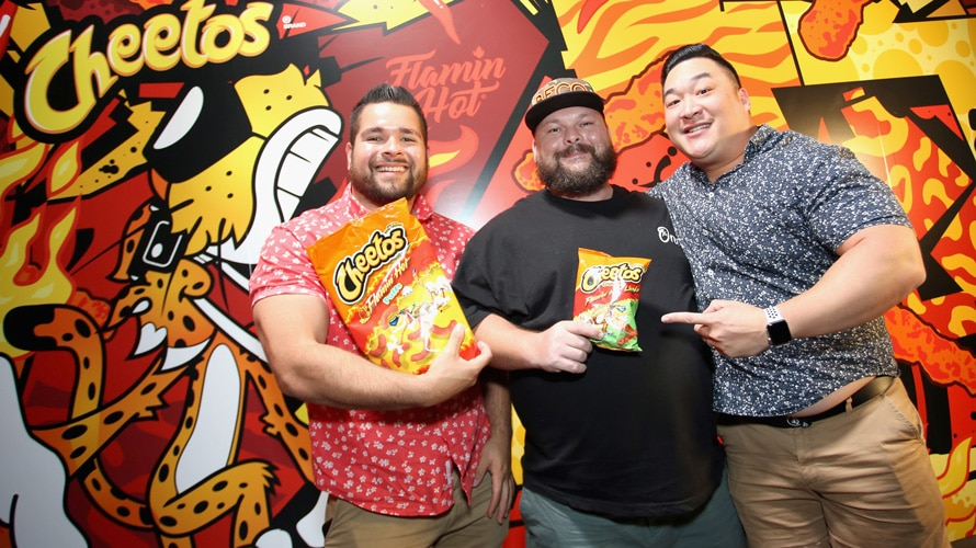 three men standing in front of a cheeto