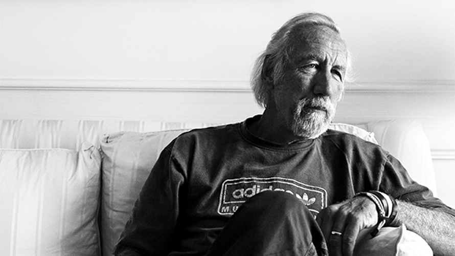 a black and white headshot of Lee Clow sitting on a couch