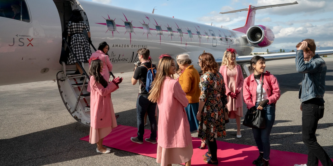 a group of women dressed in pink outfits standing in front of a plane