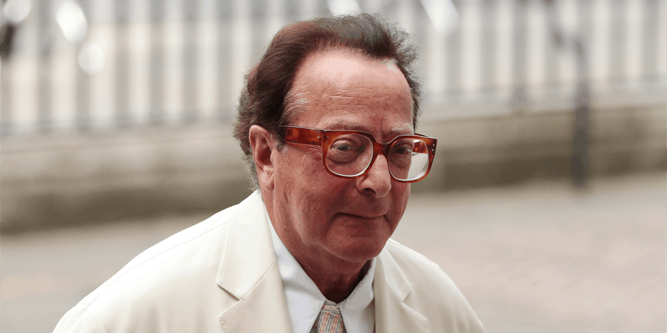 a headshot of a man in a white suit with red glasses