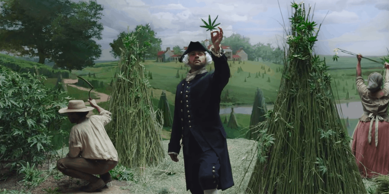 jesse williams holding a marijuana leaf in a field while people farm