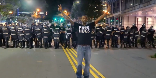 Man standing in front of a police blockade holding the peace signs with a