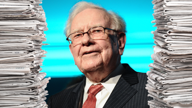 warren buffet surrounded by stacks of newspapers