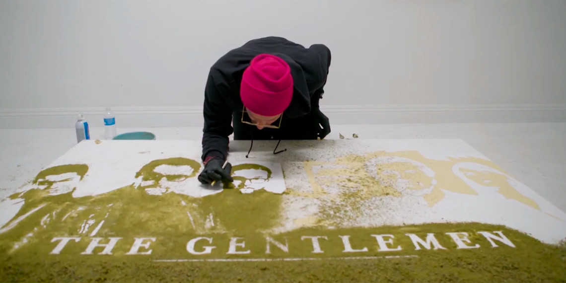 An artist bends over a poster made of cannabis with the words The Gentleman