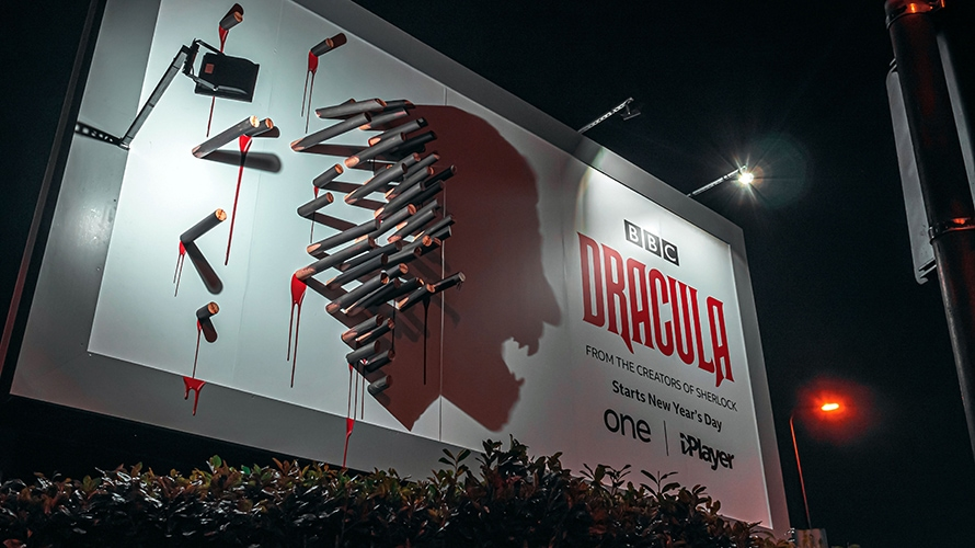 billboard with stakes casting dracula's face in shadow