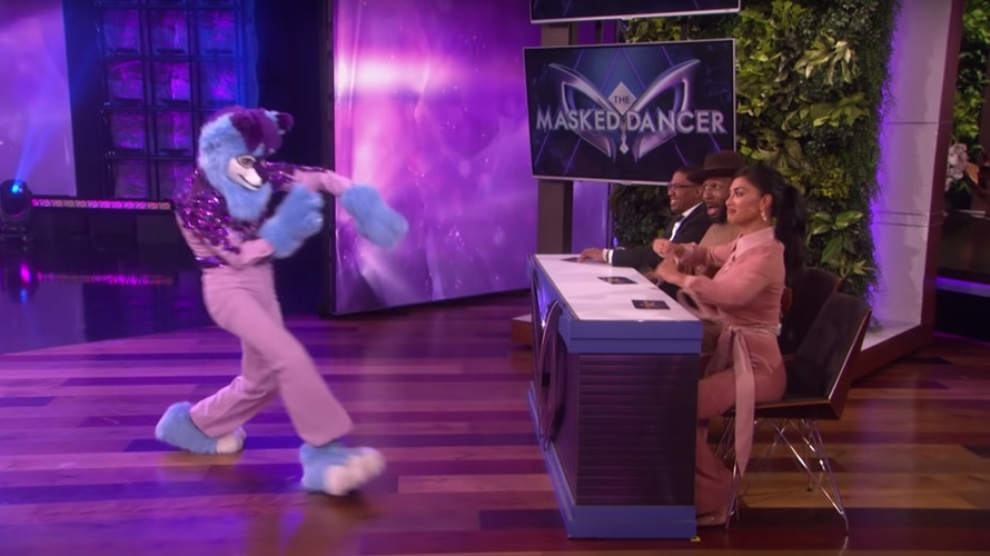 Masked dancer dancing in front of judges Nick Cannon and Nicole Scherzinger