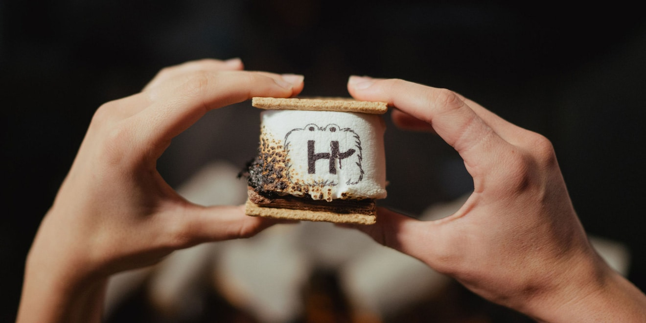 hands holding s'mores with hinge logo the marshmallow