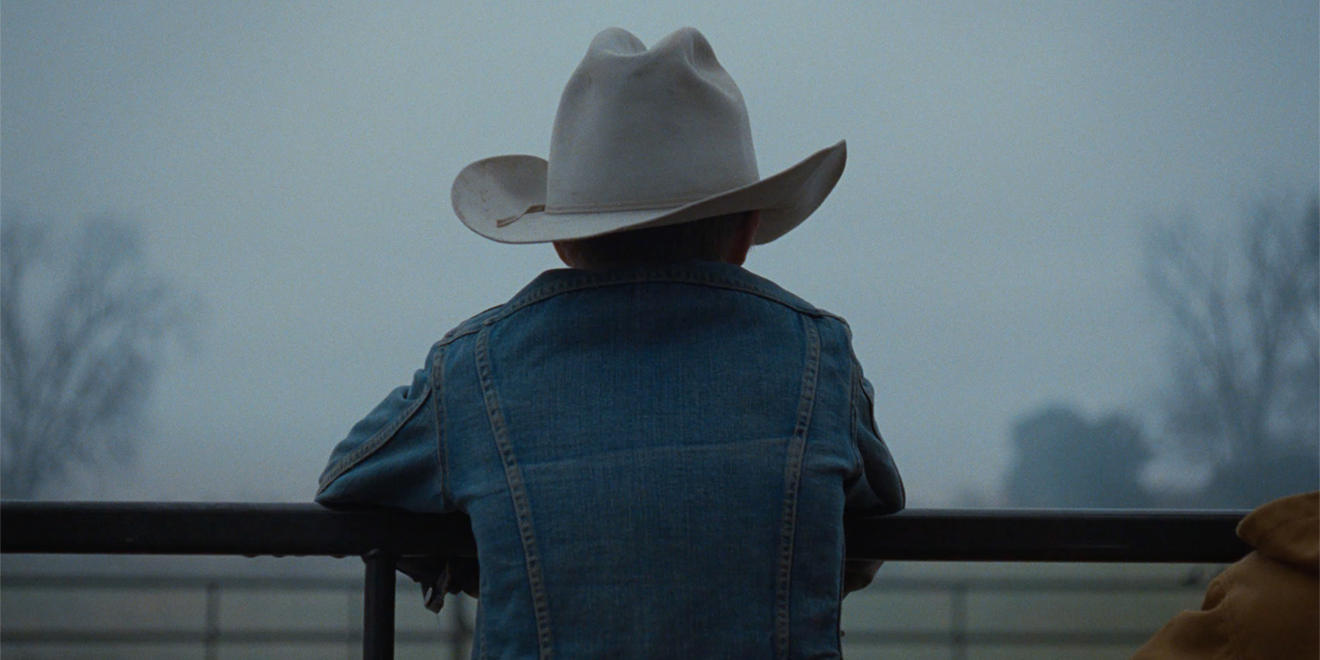 Backside of a young boy wearing a jean jacket and a cowboy hat