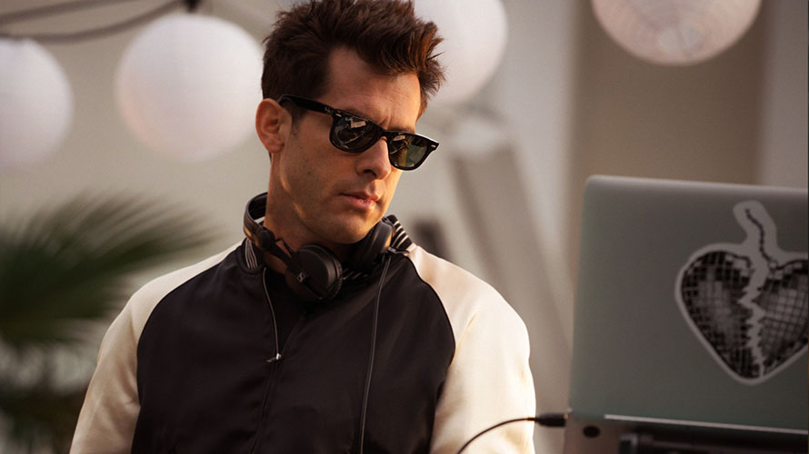 Musician Mark Ronson wearing sunglasses standing in front of a laptop