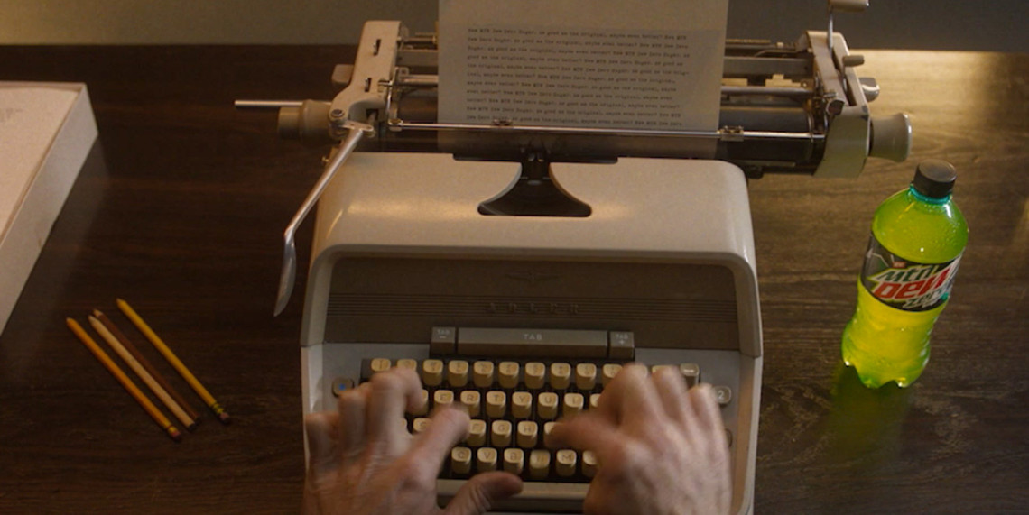 Hands typing on a typewriter; mountain dew bottle on the right side