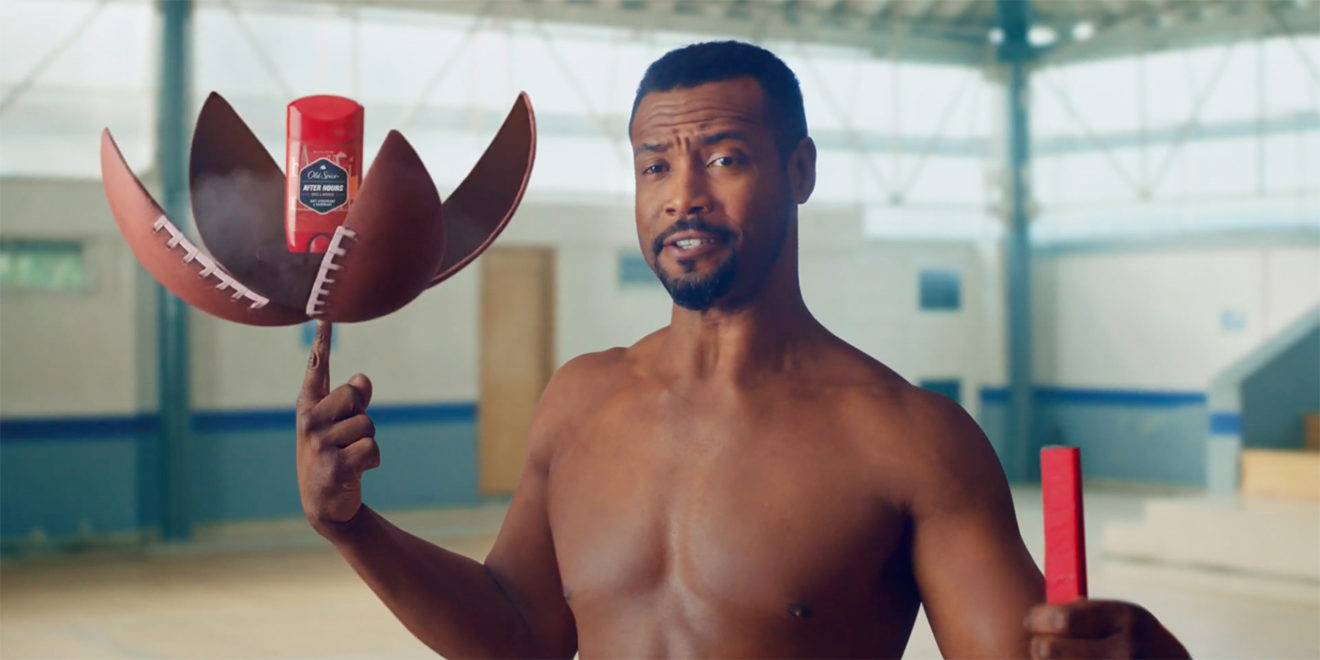 Isaiah Mustafa using his index finger to hold up a football that's open with Old Spice in the middle