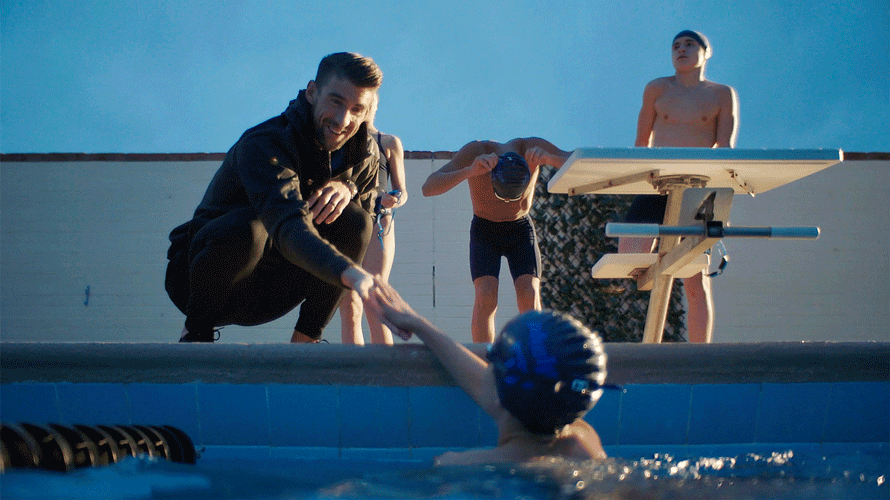 a man shaking the hand of another man in a pool with a swim cap on