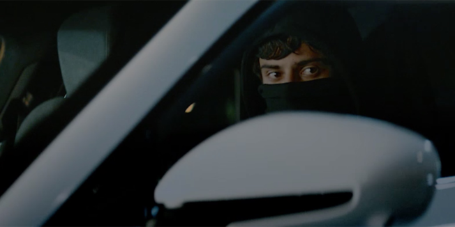 a man in a mask sitting at the wheel of a car